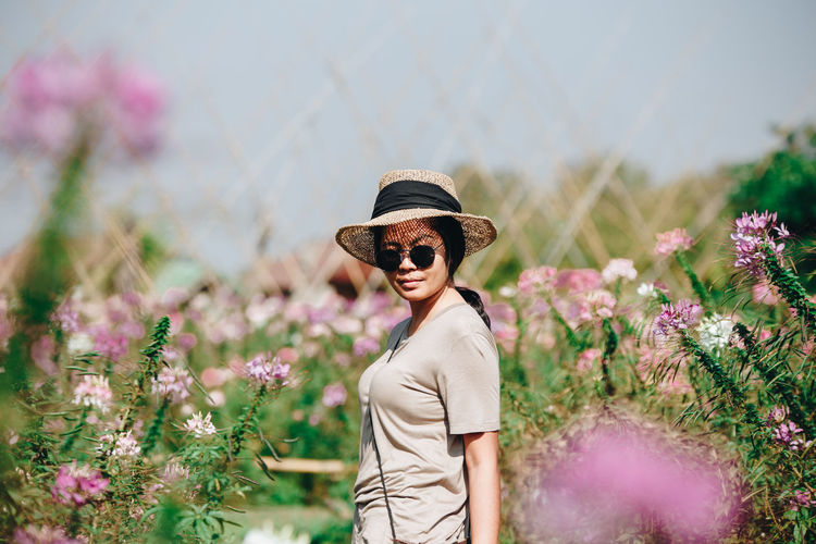 Portrait of woman wearing sunglasses while standing by flowering plants