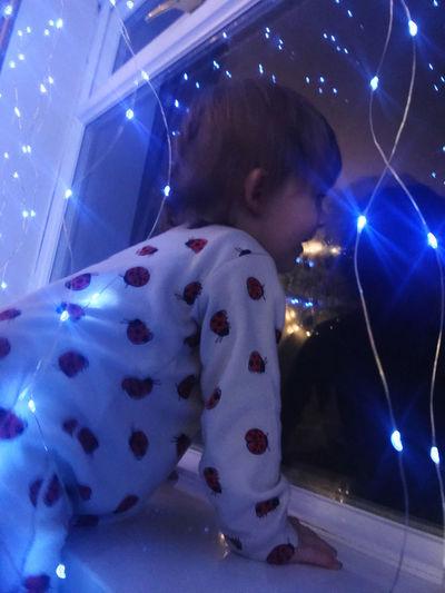 Portrait of boy looking at illuminated lights