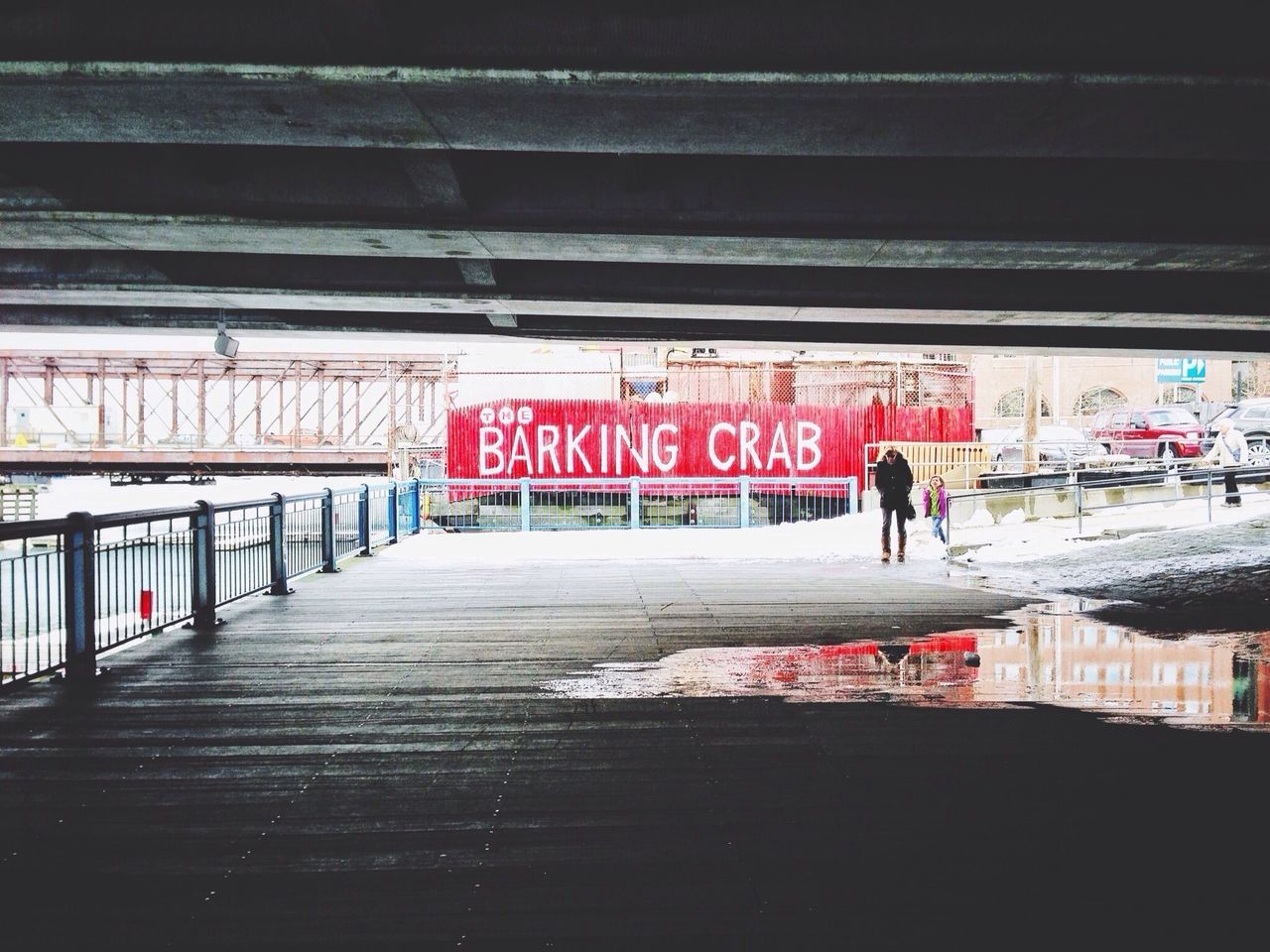 Man walking under bridge