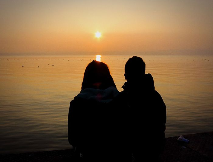 Rear View Of Silhouette Couple At Beach During Sunset