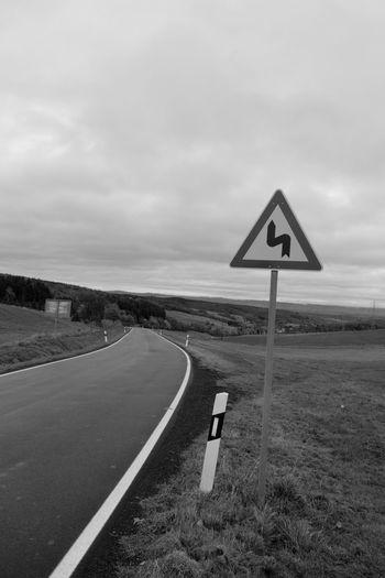 Signboard On Empty Road Along Countryside Landscape