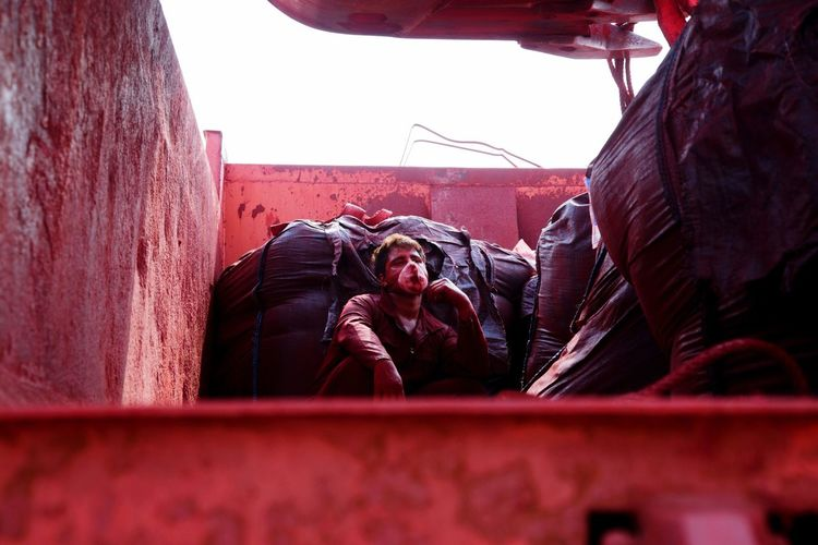 Low angle view of male worker sitting in garbage truck