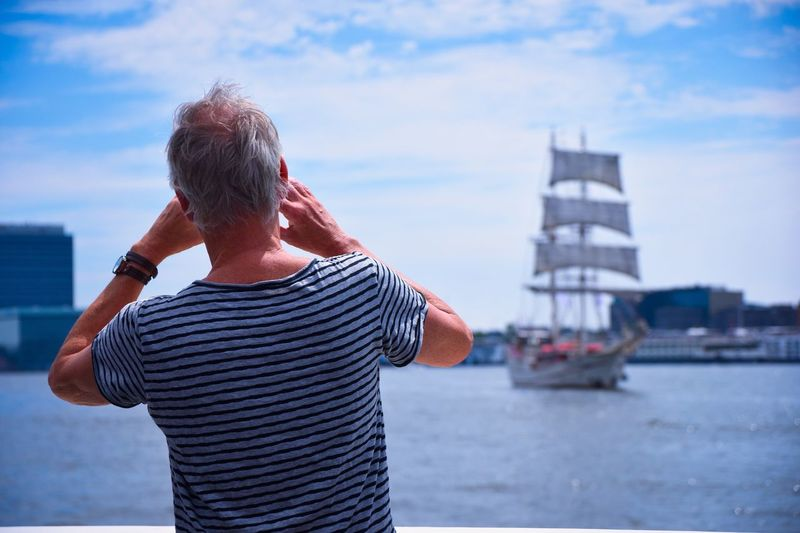 Man watching a sailship Real People Sky Sea Nautical Vessel One Person Water Rear View Leisure Activity Casual Clothing Cloud - Sky Lifestyles Ship Harbor Outdoors Day Sailing Men Sailboat Standing Vacations