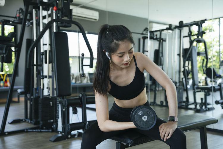 Beautiful young woman exercising at gym