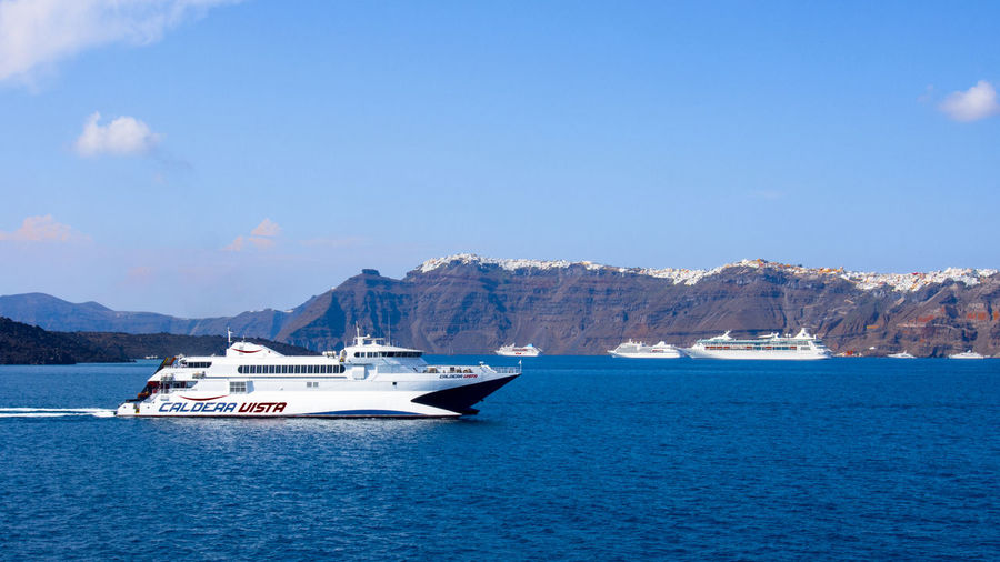 View of Fira, Santorini Island, from the Caldera, with cruise ships and ferry boats in the harbour Aegean Sea Santorini, Greece Aegean Islands Cruise Ship Nautical Vessel No People Passenger Craft Sailboat Scenics - Nature Sea Water Waterfront Yacht