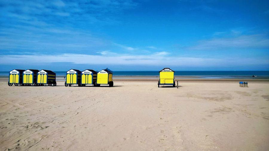 Trolleys at beach against blue sky