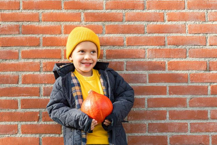 Portrait of smiling boy holding orange against brick wall