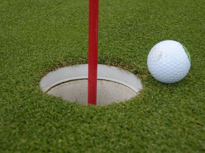 High Angle View Of Golf Ball By Flag On Grass