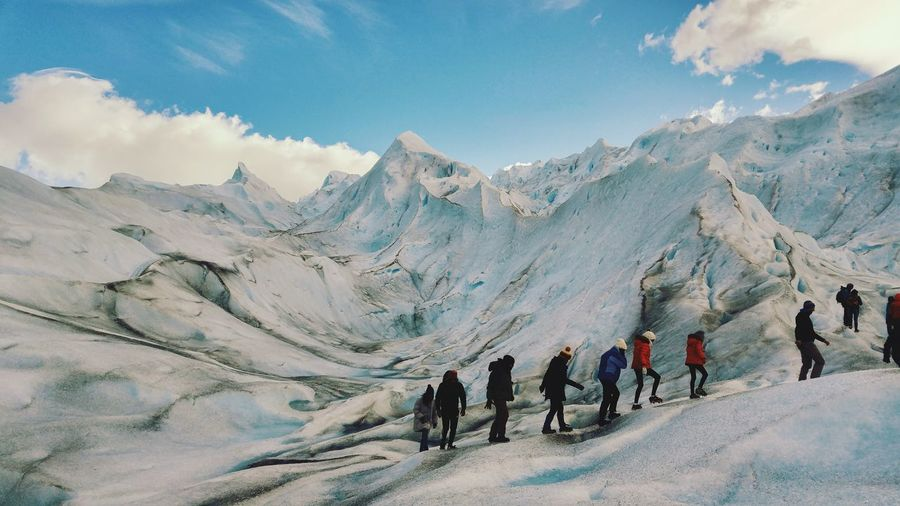Hikers walking on snowcapped mountains against sky