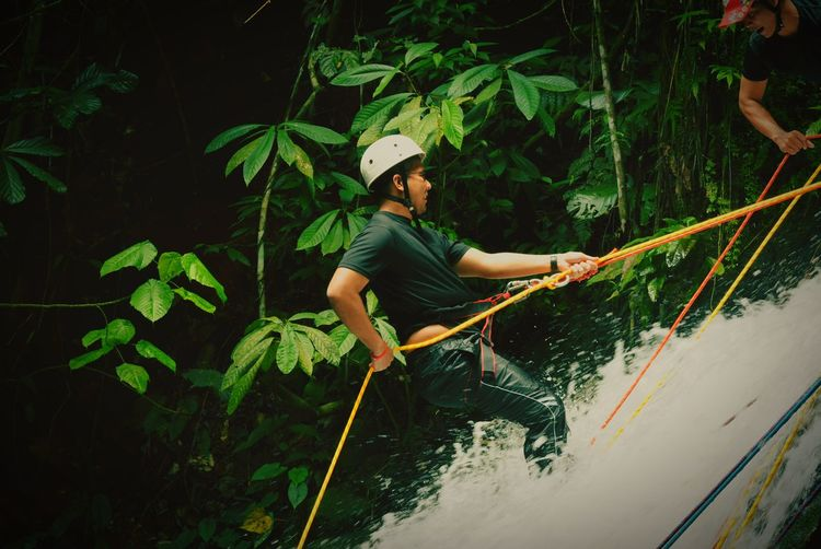 Side view of man rappelling on waterfall