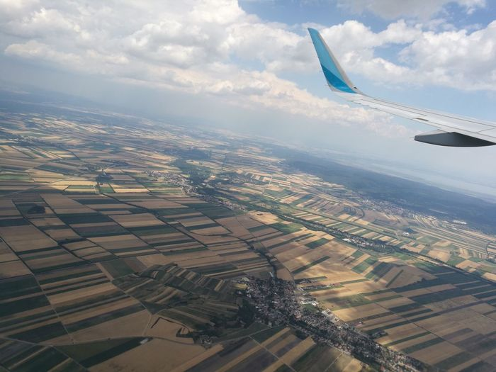 Aerial view of airplane flying over landscape against sky