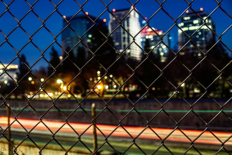 Full frame shot of chainlink fence against illuminated city at night