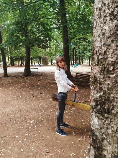 Full length portrait of girl standing by tree