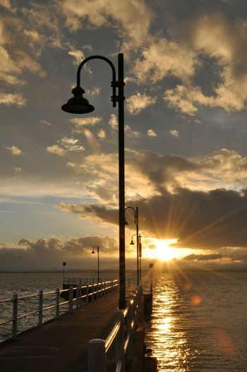 Silhouette Street Light By Sea Against Sky During Sunset