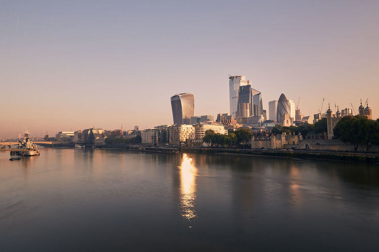 View of riverbank thames river against skyscrapers. urban skyline of london at morning light.