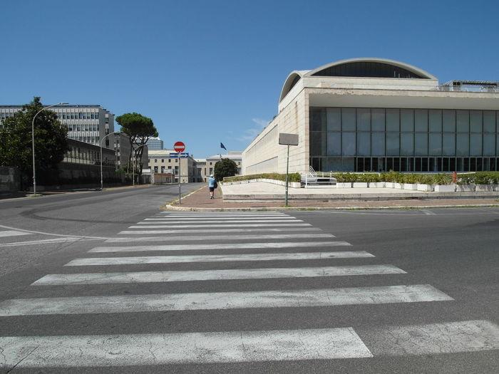 Zebra crossing road against clear sky