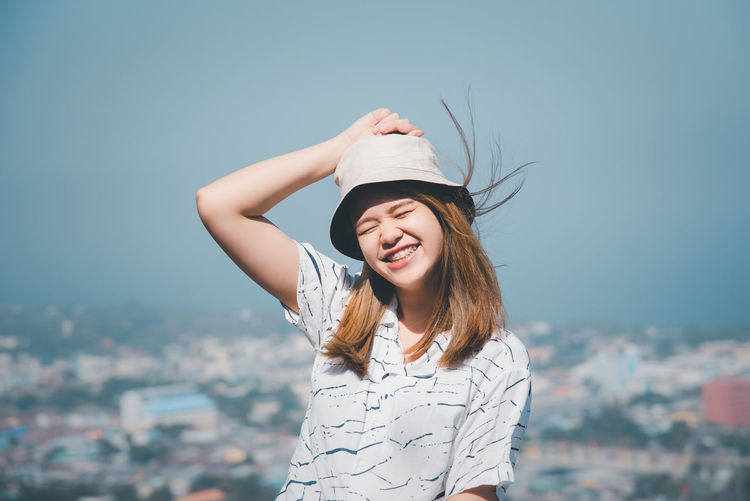 Portrait of a smiling young woman against sky