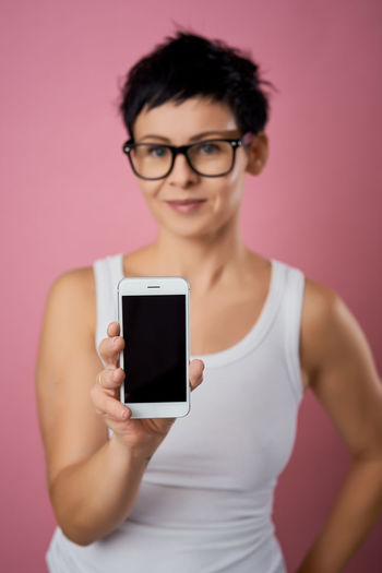 One Person Eyeglasses  Glasses Portrait Front View Technology Indoors  Looking At Camera Adult Holding Young Adult Communication Wireless Technology Women Mobile Phone Standing Smiling Lifestyles Pink Color Hairstyle Beautiful Woman Mockup