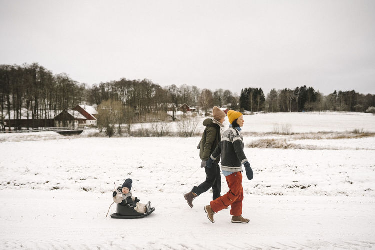 Rear view of people in winter against sky
