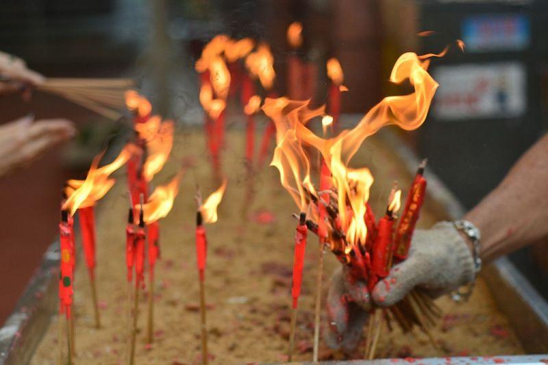 Close-Up Of Man Holding Burning Incense Sticks