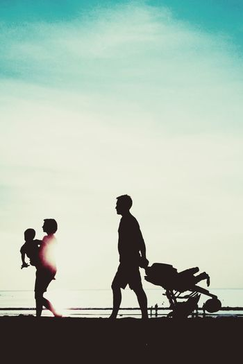 Silhouette Family Walking Against Sea During Sunset