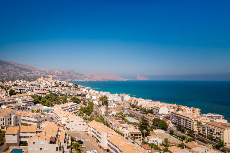 High angle view of townscape by sea against blue sky. altea, comunidad valenciana, spain
