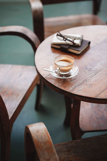High angle view of coffee cup by books on table