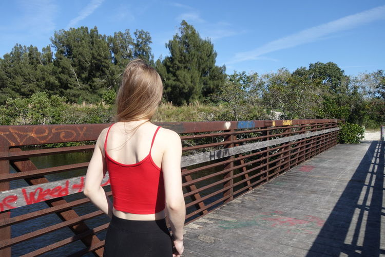 Rear view of woman standing by railing against trees