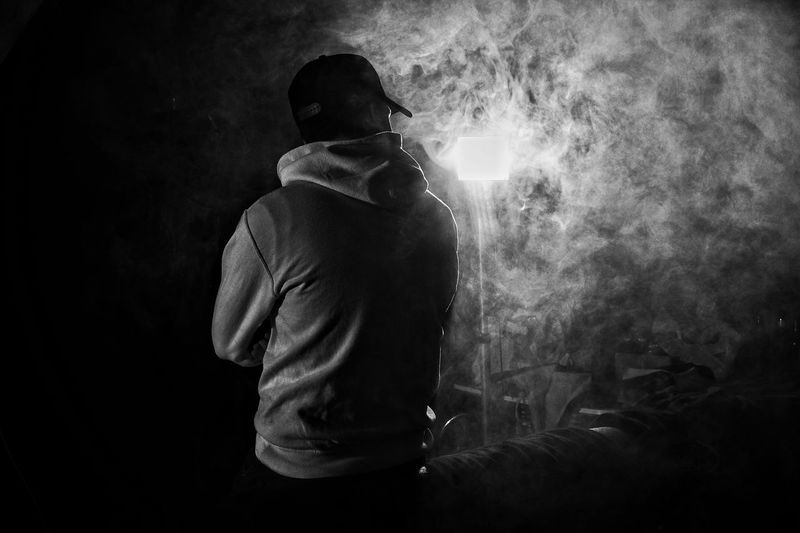 Rear view of man standing against illuminated lighting equipment