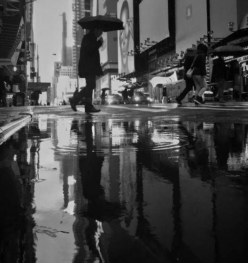 Reflection of man in puddle on city