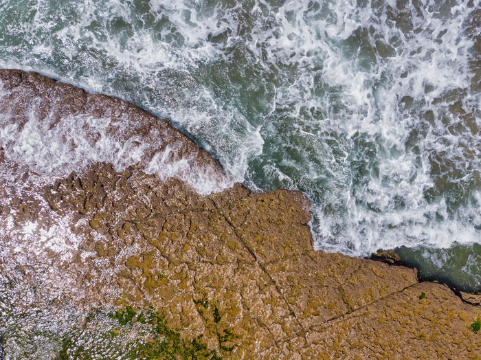 High angle view of waves breaking on rocks