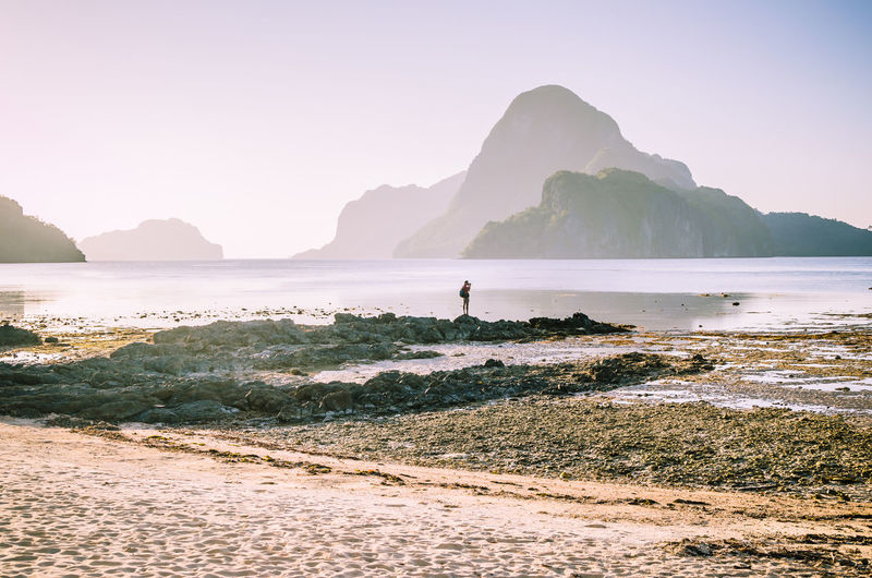 Lonely photographer on top of the rocks during low tide making photo on morning sunrise light in front of amazing Cadlao Island, El-Nido, Palawan, Philippines. Lonely Philippines Relief Shapes Silhouette Around The World Beach Bizarre Nature Cadlao Island Elnido Getaway  Idyllic Scenery Journey Low Tide Outdoors Palawan Philippines Paradise Photographer Sandybar Solitude Sunrise Surreal Tourism Unspoiled Nature Vacation Destination EyeEmNewHere