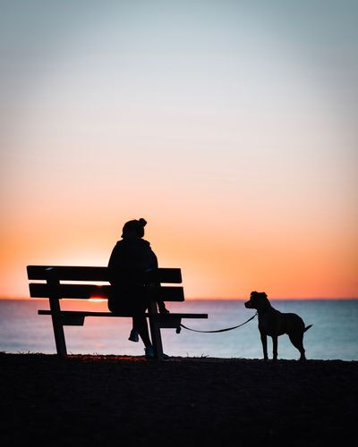 Silhouette woman with dog at beach against sky during sunset