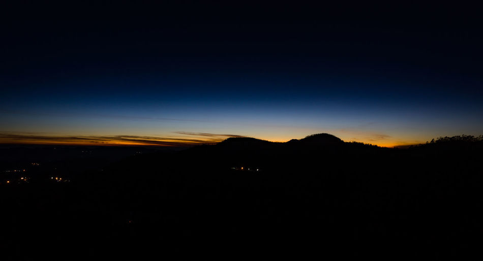 Scenic view of silhouette mountains against sky at night