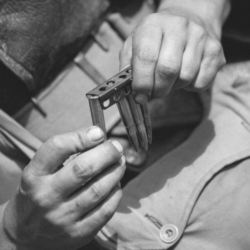 Cropped Image Of Hand Holding Bullets With Cartridge