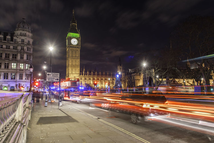 Light trails by big ben in city at night