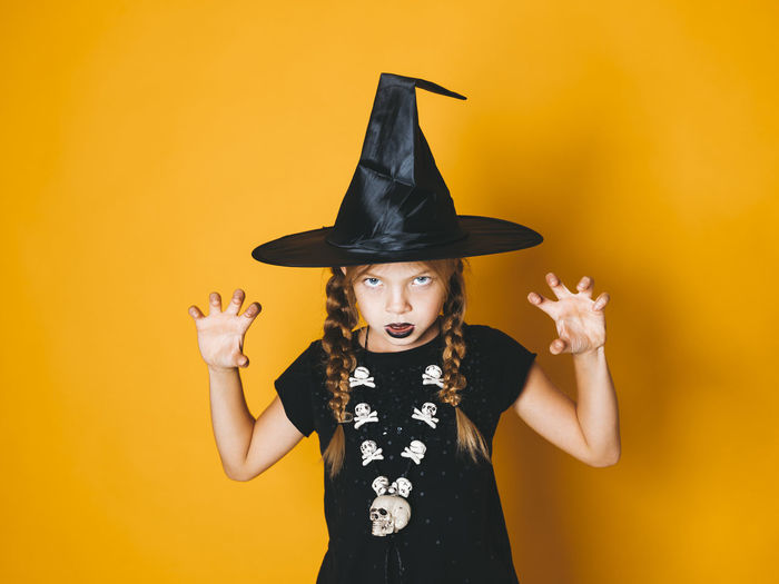 Portrait of girl wearing witch hat gesturing against yellow background during halloween