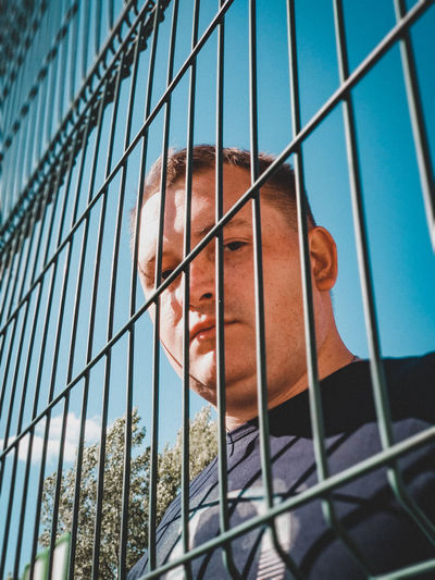 Low angle portrait of man seen through fence