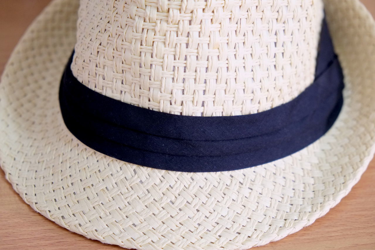 CLOSE-UP OF HAT ON TABLE AGAINST WHITE BACKGROUND