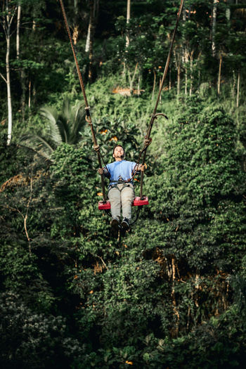 Man by plants in forest
