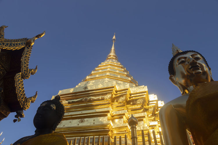 Low angle view of statue against temple building against clear sky