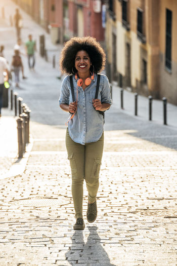 Portrait Of Smiling Young Woman Walking On Street In City During Sunny Day