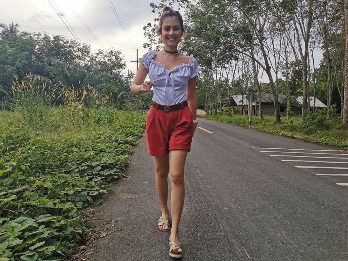 Full length portrait of woman walking on road