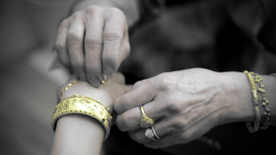 Cropped image of woman putting bracelet around brides hand