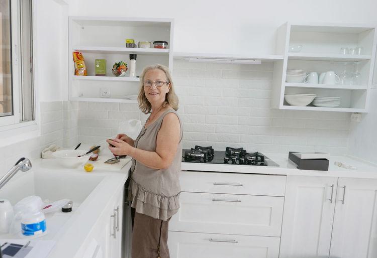 Happy woman washing crockery in kitchen