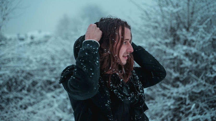 Smiling young man with snow on body standing in forest during winter