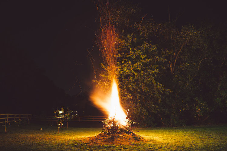 Bonfire against trees at night