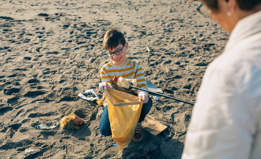 Grandmother and grandson picking up garbage at beach