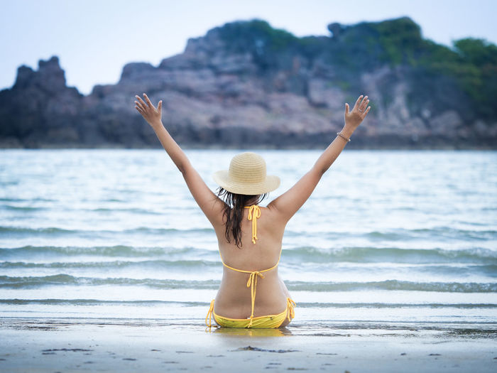 Rear view of woman wearing bikini with arms outstretched while sitting at beach