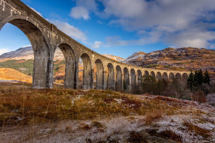 Glenfinnan Viaduct made famous by its staring role in the Harry Potter films. West Coast Highlands of Scotland Arch Architecture Beauty In Nature Bridge - Man Made Structure Built Structure Cloud - Sky Day Glenfinnan Viaduct Growth Landscape Mountain Mountains Nature No People Outdoors Scenics Scotland Sky Tranquility
